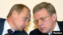 Президент Владимир Путин и министр финансов Алексей Кудрин беседуют друг с другом во время встречи министров экономики в Москве, 19 марта 2004 года