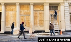 Workers put plywood over windows of stores in New York City as a precaution against potential damage from election-related protests on November 2.