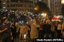 Демонстранты с фонариками в смартфонах возле минской стелы. Ночь с 9 на 10 августа
