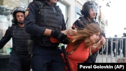 Сотрудники полиции задерживают девушку во время митинга в центре Москвы, 27 июля 2019 года