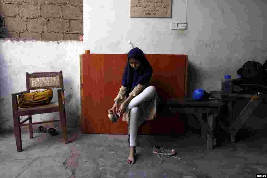 Школа расположилась в южном городе Карачи в небольшом здании под реконструкцией. 12-летняя Табиа снимает обувь после окончания тренировки
