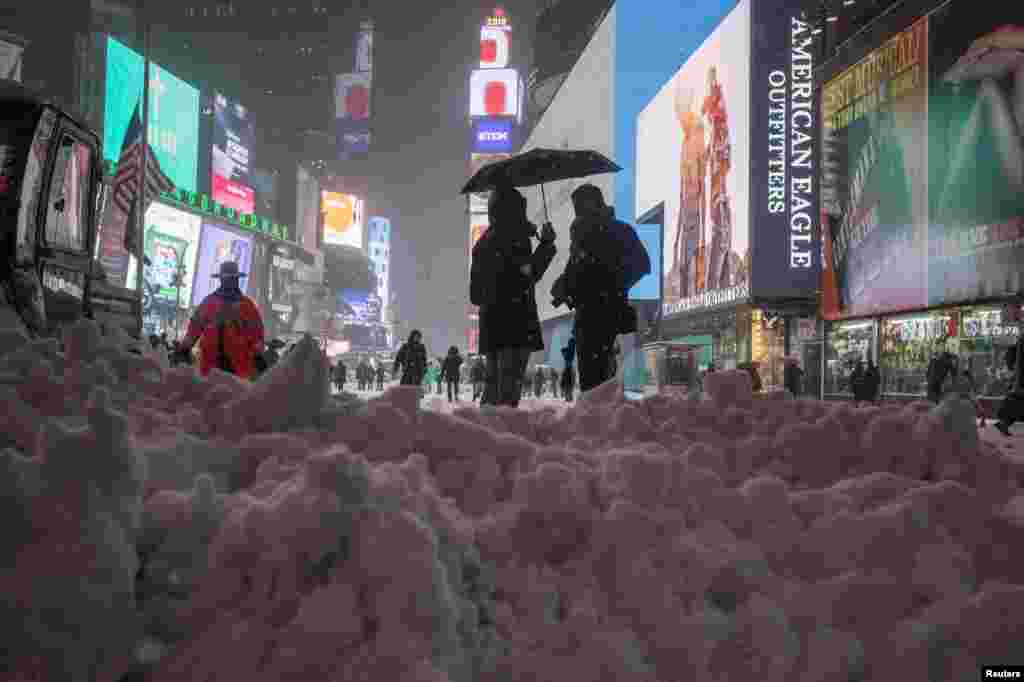 Люди стоят посреди неубранного снега на Таймс Сквер