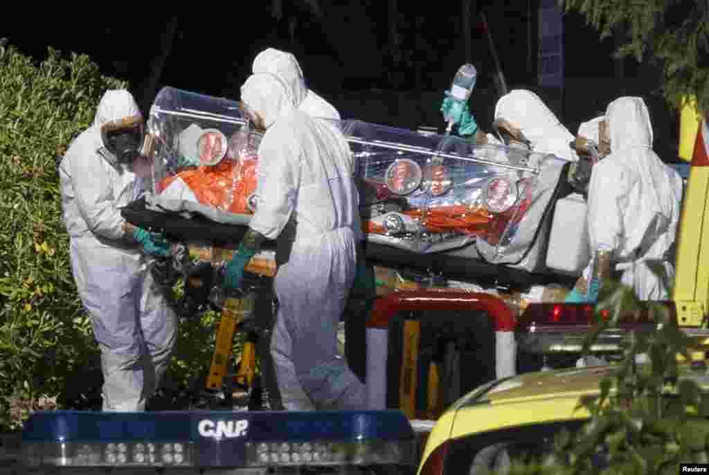 Медики в защитных костюмах эвакуируют одного из пациентов, предположительно зараженного Эболойв Либерии, сразу после прибытия в Мадрид. Испания. 7 августа 2014