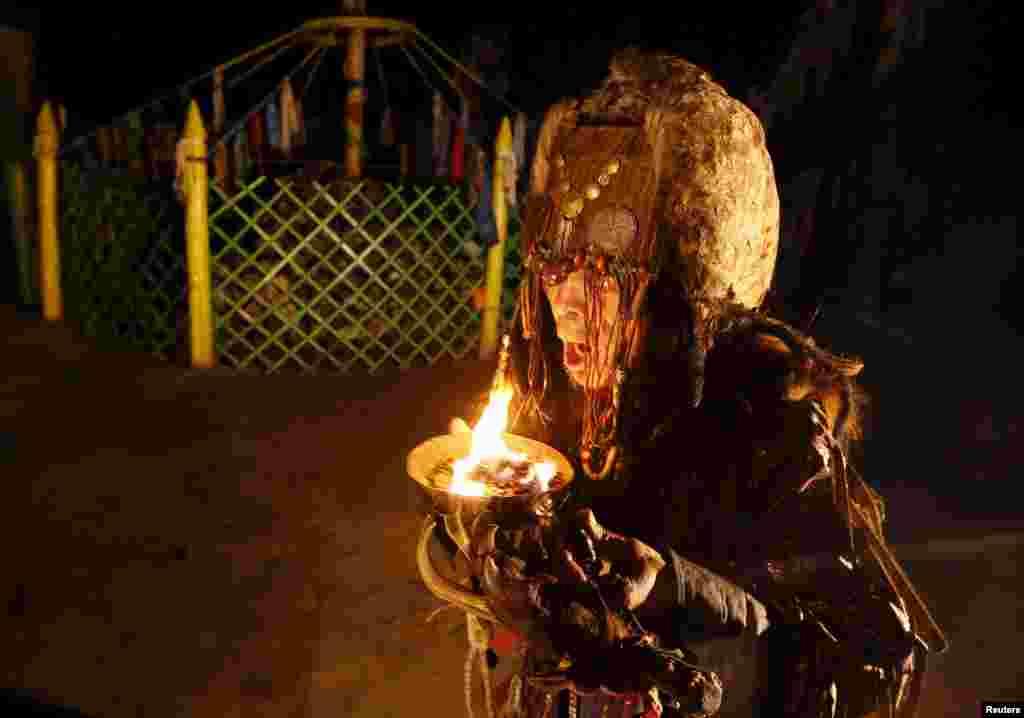 """На фото - шаман из общества Адыг Ээрен (""""Медвежий дух"""") пытается войти в транс и связаться с духами умерших через ночной ритуал камлание (священный шаманский ритуал)"""