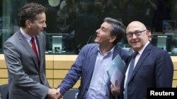 Новоназначенный министр финансов Греции Эвклид Цакалотос (в центре) с министром финансов Еврогруппы Мишелем Сапином и представителем еврокредиторов