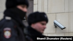 Police officers walk past a surveillance camera in downtown Moscow on January 26, 2020.