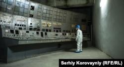 Человек смотрит на покрытый грибком пульт управления на Чернобыльской АЭС