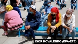 Bishkek residents wait for their turn to receive medical care near a day hospital in the Kyrgyz capital on July 6, 2020.