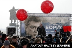 People in St. Petersburg participate in a 2018 memorial event for Boris Nemtsov, seen on the billboard.