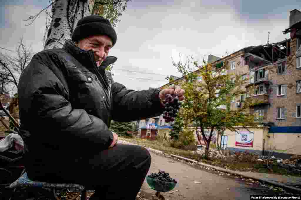 Житель Горловки - Николай - продает виноград, который он выращивает в своем саду. Население возврашается в свои дома, но найти работуочень сложно. Горловка. Украина. Октябрь 2014