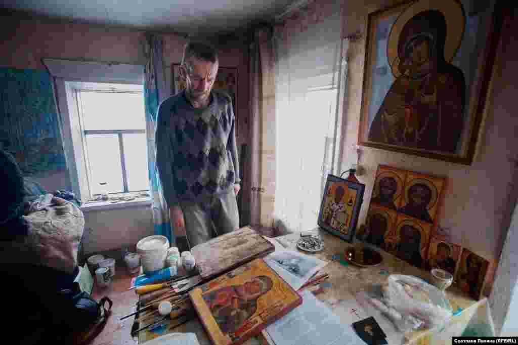 На столе – иконы, написанные Терентьевым за последний год.Рядом с готовыми работами лежат книги с правилами иконописного мастерства