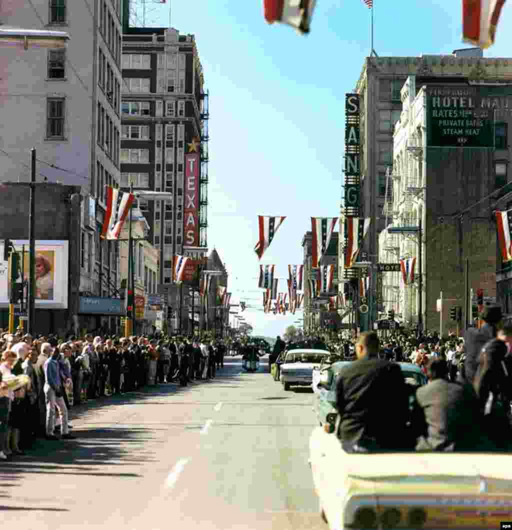 Толпы собираются на Мэйн-стрит в Далласе в ожидании президентского кортежа. Он движется к району Дили Плаза, где и произойдет убийство.