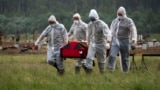 Virus Outbreak Russia -- file -- Cemetery workers wearing protective suits carry the coffin of a COVID-19 victim in the special purpose for coronavirus victims section of a cemetery in Kolpino, outside St.Petersburg, Russia, Tuesday, June 30, 2020.