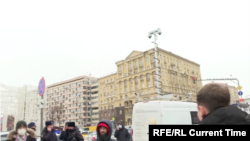 Current Time correspondent Aleksei Aleksandrov (bottom right) shows an unmarked white van equipped with a surveillance camera in downtown Moscow during the city's January 31, 2021 protest for the release of Aleksei Navalny.