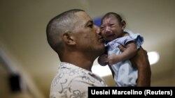 Бразилец держит в руках сына с микроцефалией, 26 января 2016