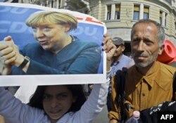 Мигрант держит в руках постер с фотографией Ангелы Меркель, Венгрия, 4 сентября 2015