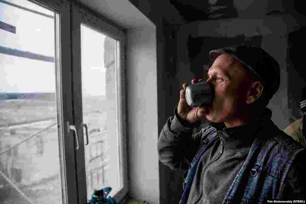 Строитель пьет чай во время обеденного перерыва