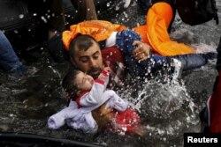 Беженец из Сирии пытается удержать ребенка во время падения на берегу у острова Лесбос. 24 сентября 2015