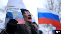 A woman with a copy of the Russian constitution takes part in a February 29, 2020 march in memory of murdered Kremlin critic Boris Nemtsov in downtown Moscow.
