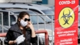 Kazakhstan - A woman wearing a protective face mask walks past the warning sign, placed near the residential building quarantined in response to the spread of coronavirus disease (COVID-19) in Almaty, Kazakhstan March 24, 2020. REUTERS/Pavel Mikheyev