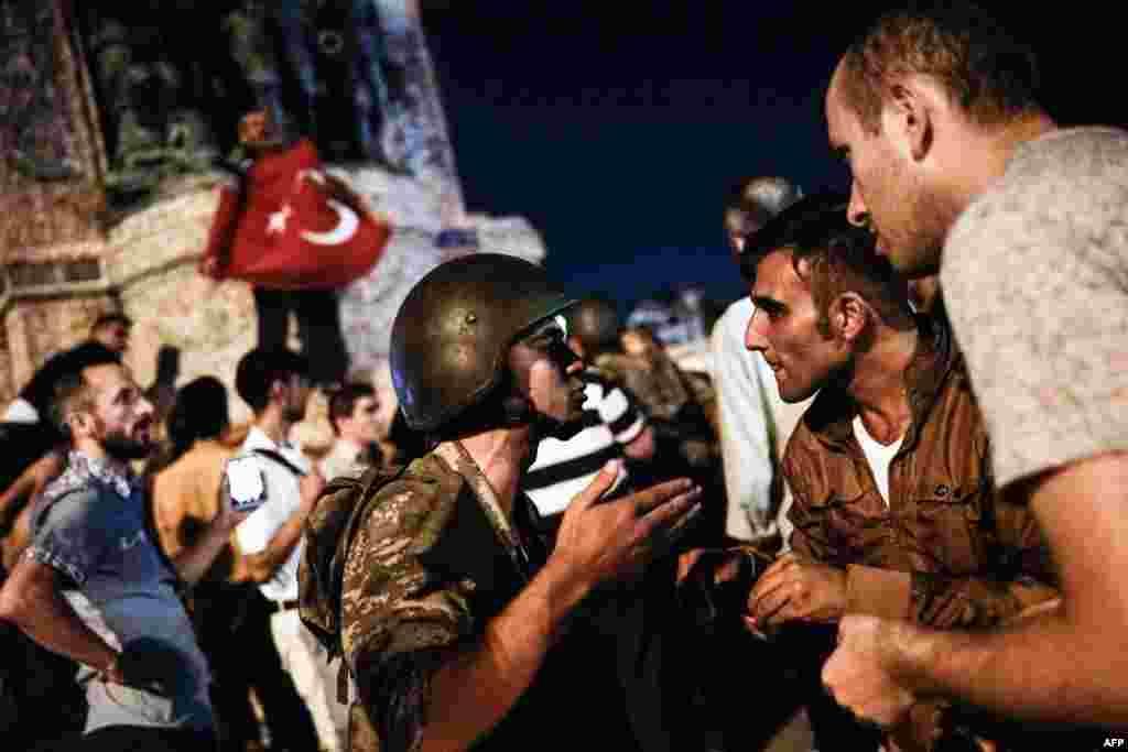 Турецкие граждане обращаются к военнослужащему на площади Таксим в центре Стамбула, куда они пришли после начала военного переворота