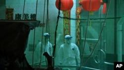 Медработники в специальных защитных костюмах во время эвакуации жителей дома в Гонконге
