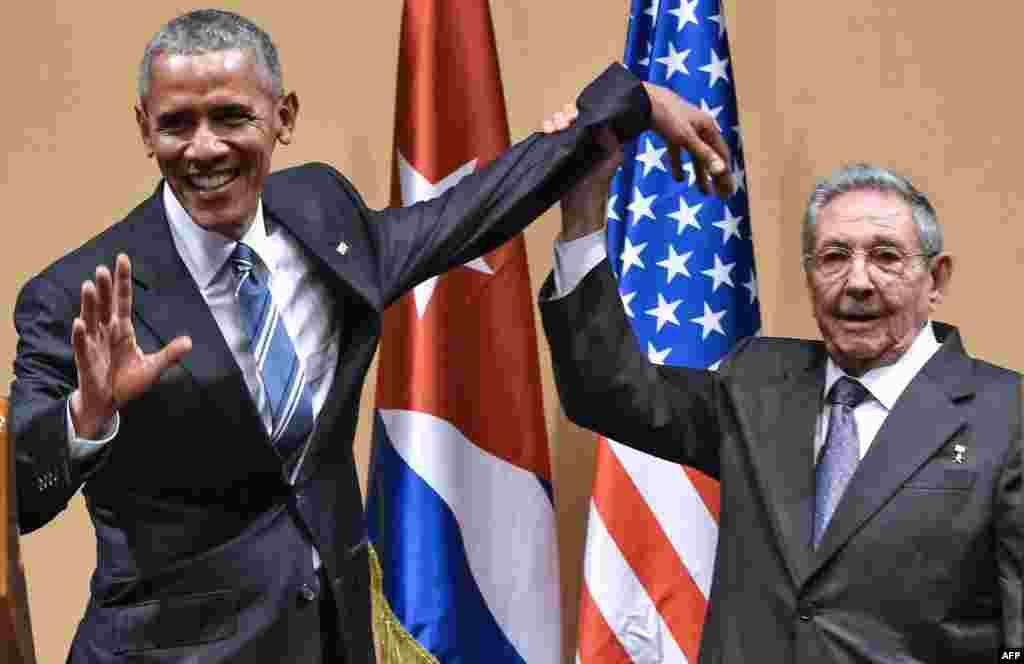 Президент Кубы Рауль Кастро поднимает руку Обамы во время встречи во Дворце Революции в Гаване 21 марта 2016 года. Обама стал первым президентом США, который приехал на Кубу после революции 1959 года, отметив тем самым потепление отношений между двумя странами.