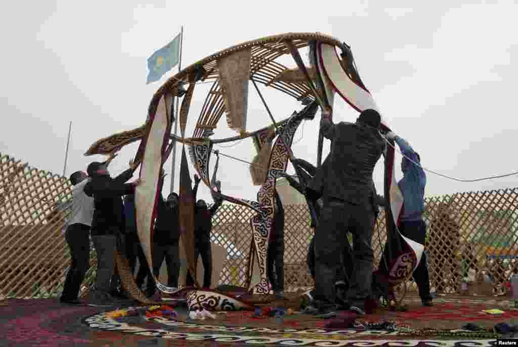 Мужчины разбирают юрту, поставленную к празднованию Навруза. Казахстан