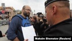 Полицейский зачитывает постановление муниципальному депутату Илье Азару
