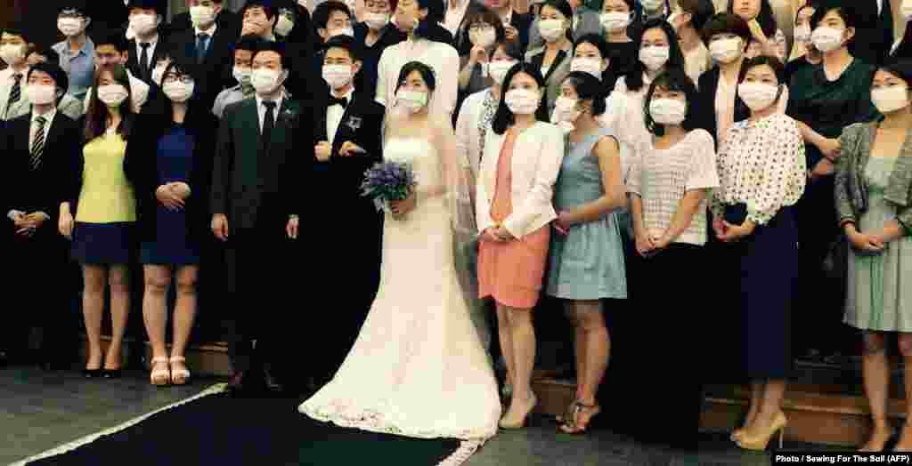На фото - свадебная церемония в масках. Пара стала негласным символом южнокорейской эпидемии