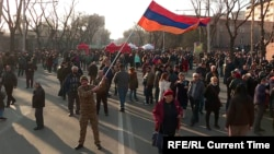 A protester waves the Armenian flag in downtown Yerevan on March 1 at ongoing demonstrations for Armenian Prime Minister Nikol Pashinian's resignation.