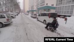 Андрей Виноградов на улице в Томске. Передвигаться на коляске приходится по проезжей части: на тротуаре коляска застревает в снегу