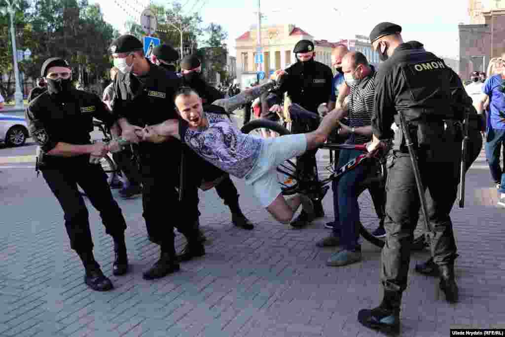 """Задержание велосипедиста во время акции протеста в Минске, 19 июня. По всей стране прошли последние пикеты по сбору подписей за выдвижение кандидатов в президенты, а также акции солидарности с задержанными политическими активистами и претендентом на пост президента Виктором Бабарико. По информации правозащитного центра """"Весна"""", в Минске задержали более 150 человек."""