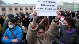 """RUSSIA – A demonstrator holds up a sign reading """"today they kill Navalny, tomorrow they kill me"""" during a rally in support of jailed Russian opposition politician Alexei Navalny in Moscow, April 21, 2021"""