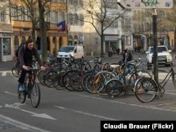 Велосипедист и припаркованные велосипеды на улице в центре Страсбурга