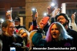 Когда стало смеркаться, участники акции зажгли фонарики своих мобильных телефонов и подняли их вверх. Фото: Reuters