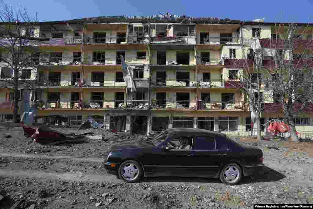 Before the arrival of Azerbaijani troops, a man drives a car past a building reportedly damaged from shelling of the Karabakhi town of Shushi (Shusha) in late October 2020.  Badly damaged buildings from the first Karabakh war in the early 1990s can still be found throughout the town.