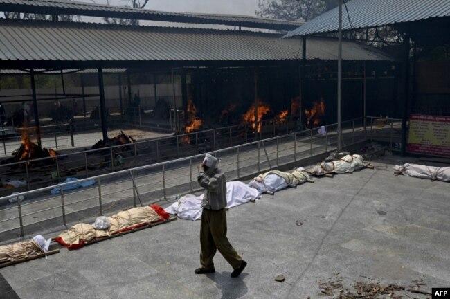 Человек идет мимо приготовленных к кремации тел умерших от COVID-19. Нью-Дели, Индия, 28 апреля 2021 года. Фото: AFP