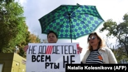 """A woman holds a placard reading """"You can't shut up everyone!"""" as journalists and supporters on September 4, 2021take part in a Moscow protest against the Russian government's list of """"foreign agent"""" media."""