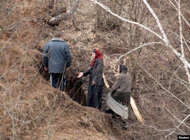"""Женщины из числа пензенских затворников и представитель администрации села Никольского Пензенской области возле входа в пещеру, 29 марта 2008 года. Восемь женщин к этому времени покинули """"затвор"""", другие оставались под землей. Фото: Reuters"""