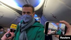 Russian opposition leader Aleksei Navalny boards a January 17, 2021 flight from Berlin to Moscow after completing medical treatment in Germany for a Novichok nerve-agent poisoning.