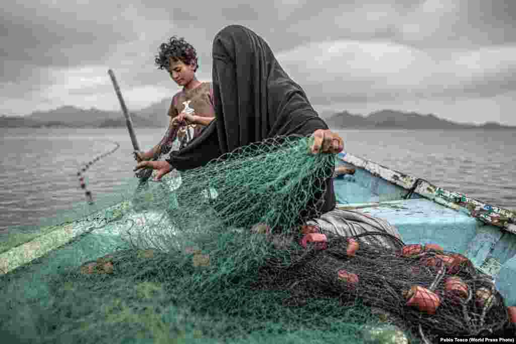 """Фатима с сыном готовят рыболовную сеть, Йемен (12 февраля 2020). У Фатимы девять детей, на жизнь она зарабатывает рыболовством. Несмотря на то, что ее деревня была разрушена войной, она вернулась, чтоб начать новую жизнь.Конфликт междуповстанцами-хуситами (шиитами)и коалицией арабов-суннитов во главе с Саудовской Аравией начался в 2014 году ипривел, по мнению ЮНИСЕФ, к """"крупнейшему гуманитарному кризису в мире"""". Первое место в категории""""Проблемы современности"""", автор – Пабло Тоско"""
