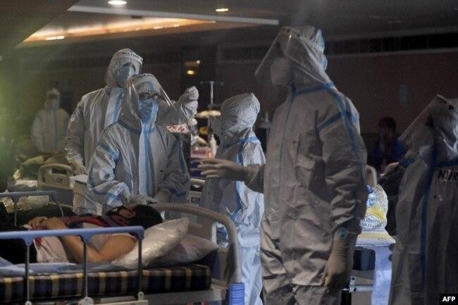Врачи в защитных костюмах в банкетном зале, временно переоборудованном для лечения пациентов с COVID-19. Нью-Дели, Индия, 29 апреля 2021 года. Фото: AFP