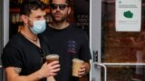 People wear masks against the coronavirus disease (COVID-19), following the CDC recommendation that fully vaccinated Americans wear masks as the highly transmissible Delta variant has led to a surge in infections, in Times Square in New York City, New Yor