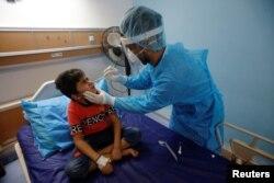 Тестирование на COVID-19 пациента онкологического отделения детской больницы в Басре, Ирак. Фото: Reuters