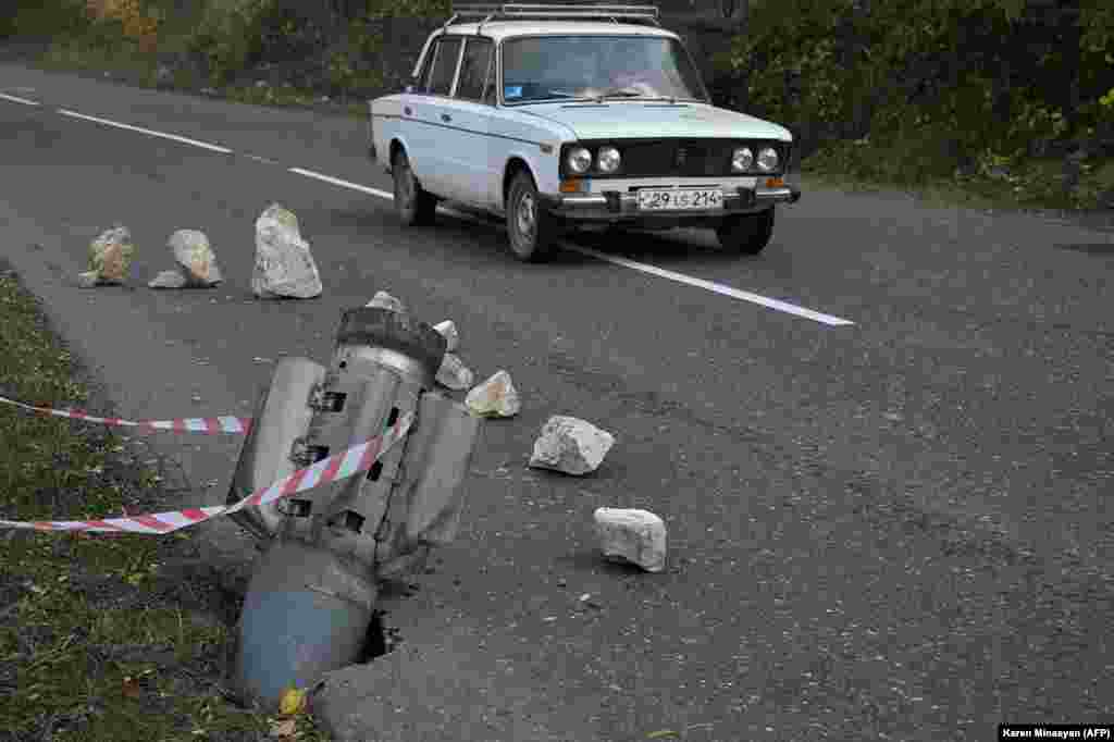 A car drives past the remains of a rocket shell near Shushi (Shusha) in late October 2020. Until 2017, the twisty, two-lane mountain road running from Karabakh's main town, Stepanakert, through Shushi was the only way for local residents to reach Armenia.