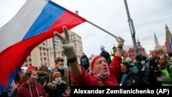 A supporter waves a Russian flag and shouts slogans during the April 21, 2021 rally in Moscow in support of jailed opposition leader Aleksei Navalny..
