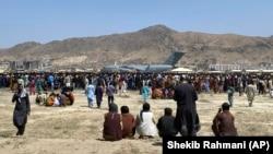 Тысячи людей в ожидании у самолета вооруженных сил США на краю аэропорта Кабула, 16 августа 2021 года