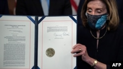 U.S. House of Representatives Speaker Nancy Pelosi (Democrat-California) displays the signed Article of Impeachment against President Donald Trump on January 13, 2021.