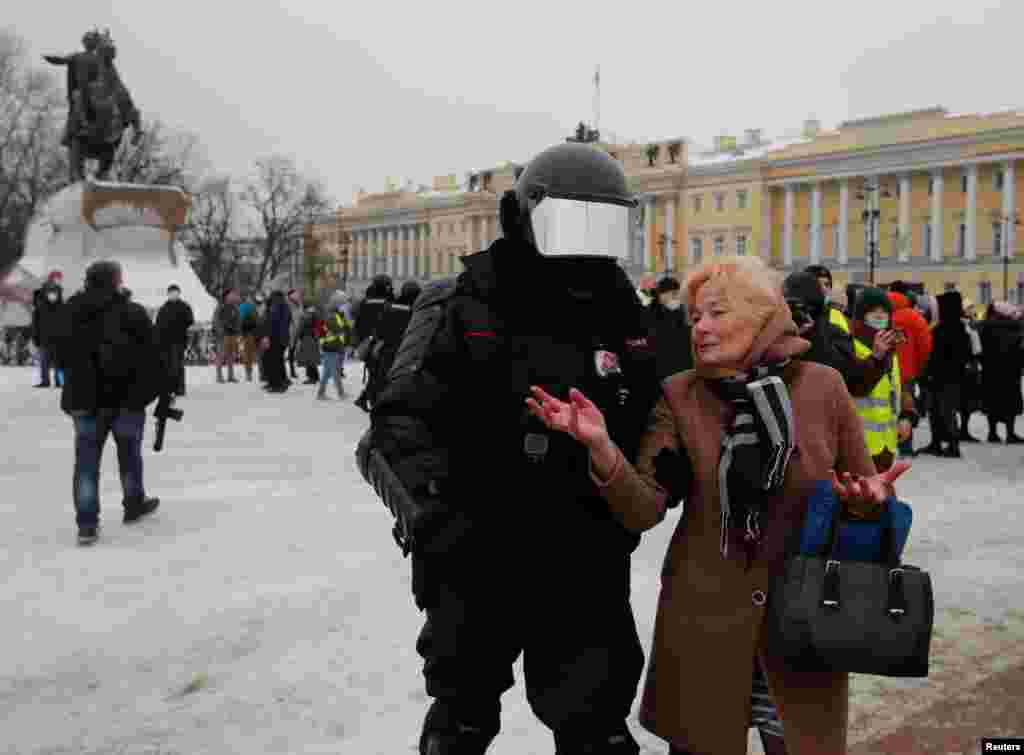 With a statue of Peter the Great in the background, riot police in St. Petersburg detain a woman on the city's Senate Square, the historic site of an 1825 revolt against Tsar Nicholas I.
